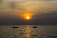 Barco de plátano del montar a caballo del grupo de personas en el mar con puesta del sol Fotos de archivo