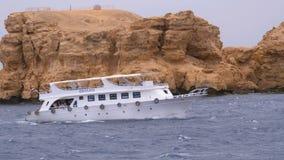 Barco de prazer com as velas dos turistas no mar tormentoso no fundo das rochas Egypt video estoque