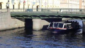 Barco de prazer com nadadas dos turistas no canal de rio de St Petersburg sob a ponte com tráfego de cidade e pedestres filme