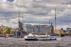 Barco de prazer no fundo da Aurora do cruzador em seu lugar da amarração na frente da faculdade de Nakhimov em St Petersburg Imagem de Stock Royalty Free