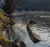 Barco de río hundido en la costa de un río foto de archivo