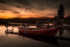 Barco de rowing en el lago en la puesta del sol imagen de archivo