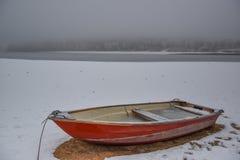 Barco de rowing rojo anclado en el lago de niebla en invierno Fotos de archivo