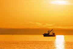 Barco de Shrimping en la puesta del sol en el océano Imágenes de archivo libres de regalías