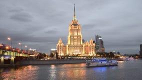 Barco de turista na frente do ` Radisson real, ` do hotel de Ucrânia do ` do ` de Moscou, no crepúsculo Noite Moscovo filme
