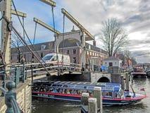 Barco de turista sob a ponte no canal da cidade em Amsterdão, Holanda, Países Baixos foto de stock