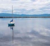 Barco de vela azul y blanco solitario en puerto Imágenes de archivo libres de regalías