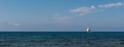 Barco de vela blanco en el horizonte Imágenes de archivo libres de regalías