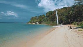 Barco de vela, catamarán, en la playa tropical con agua azul almacen de metraje de vídeo
