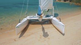 Barco de vela, catamarán, en la playa tropical con agua azul metrajes