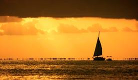 Barco de vela contra una puesta del sol hermosa Foto de archivo