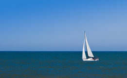 Barco de vela en el mar contra el cielo claro, azul. fotos de archivo
