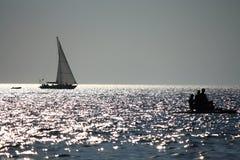Barco de vela en la puesta del sol. Fotos de archivo