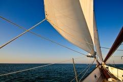 Barco de vela en la puesta del sol Fotos de archivo