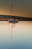 Barco de vela en luz del amanecer Fotografía de archivo