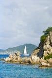 Barco de vela en paisaje costero   Fotografía de archivo