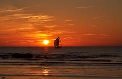 Barco de vela en puesta del sol Fotografía de archivo