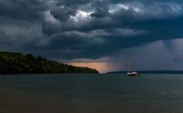 Barco de vela de la tormenta del barco de vela que viene en el lago imagenes de archivo