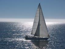 Barco de vela que se desliza en el mar tranquilo Imagen de archivo libre de regalías