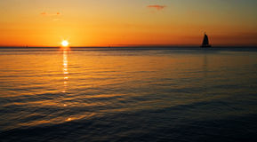 Barco de vela y puesta del sol Imagen de archivo libre de regalías