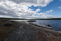 Barco de Whie na costa rochosa do lago Fotografia de Stock Royalty Free