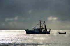 Barco del barco rastreador de la pesca en puesta del sol tempestuosa del puerto Foto de archivo libre de regalías