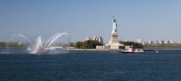 Barco del cuerpo de bomberos de New York City y estatua de la libertad Foto de archivo libre de regalías
