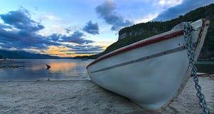 Barco del pescador en la puesta del sol en el lago fotos de archivo