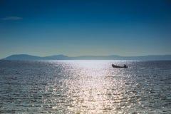 Barco del pescador que flota en el mar en un fondo de montañas Fotos de archivo