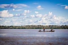 Barco del río Amazonas con el cielo azul y las nubes Foto de archivo