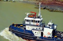 Barco del tirón del Canal de Panamá que ayuda a los buques de carga imagenes de archivo