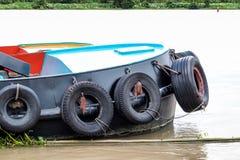 Barco del tirón con la defensa de los neumáticos en el río fotos de archivo