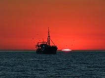 Barco delante de una puesta del sol en el horizonte Fotografía de archivo
