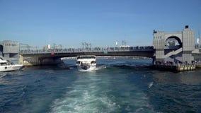Barco do cruzeiro da excursão de Bosphorus que passa sob a ponte de Galata com os turistas e os passageiros a bordo, Istambul, Tu vídeos de arquivo