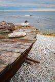 Barco do esquife na praia de pedra pelo oceano imagens de stock royalty free