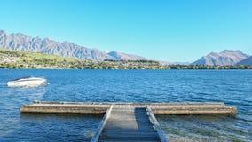 Barco e cais no lago Wakatipu Foto de Stock