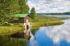 Barco e casa de madeira no lago em Finlandia Fotografia de Stock Royalty Free