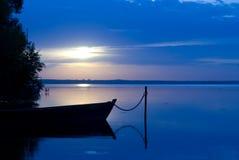 Barco e lago no crepúsculo Imagem de Stock