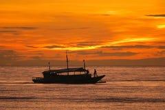 Barco e pescadores de pesca sob um nascer do sol brilhante da ilha imagem de stock royalty free