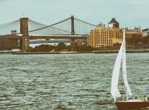 Barco em New York com a ponte de Brooklyn e de Manhattan no backgroun Fotos de Stock Royalty Free