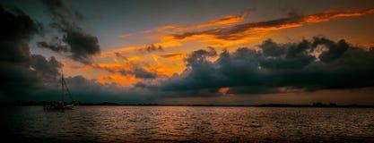 Barco em um por do sol nebuloso fotos de stock