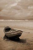 Barco em uma praia no sepia imagem de stock