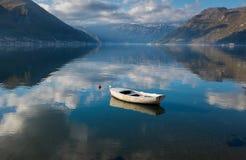Barco en claro tranquilo por completo del agua del cielo con el fondo de las montañas Foto de archivo libre de regalías