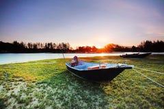 Barco en el agua de superficie durante puesta del sol Fotos de archivo libres de regalías