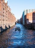 Barco en el canal en medio de edificios en el distrito viejo Speicherstadt del almacén en Hamburgo Fotos de archivo