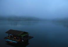 Barco en el lago en la niebla de la mañana Imagen de archivo