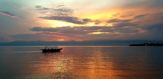Barco en el lago - puesta del sol ardiente hermosa fotos de archivo libres de regalías