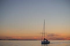 Barco en el mar cuando puesta del sol imagenes de archivo