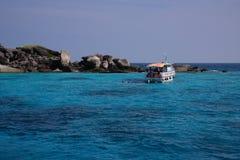 Barco en el mar hermoso y la isla tropical con el wat cristalino Foto de archivo libre de regalías