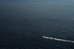 Barco en el mar, monta?a en el fondo del mar imagenes de archivo